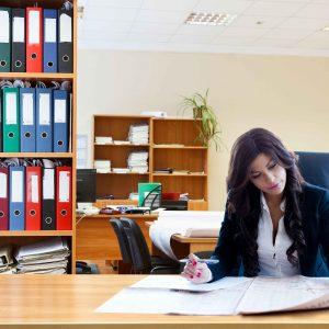 Chica leyendo periódico en una oficina
