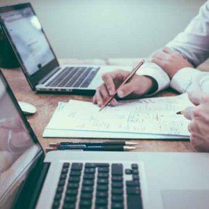 Dos personas junto a ordenador y apuntes