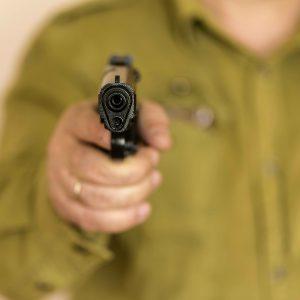 hombre apuntando a cámara con una pistola
