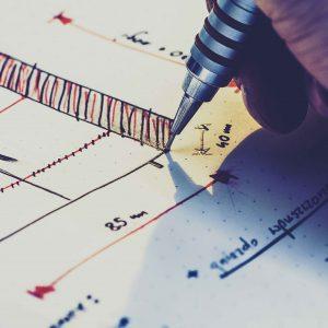 Persona diseñando planos a mano