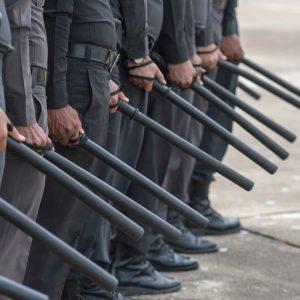 Fila de policías con bastón extensible en la mano