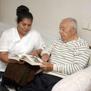 Chica ayudando a leer una revista a anciano