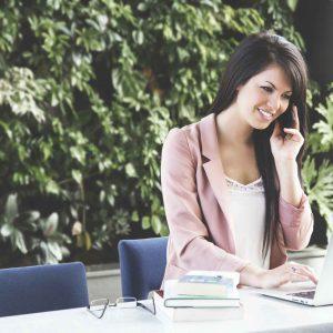 Chica hablando por teléfono mientras trabaja en portátil