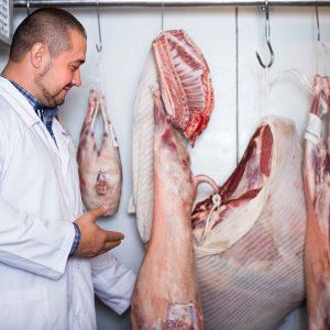 Carnicero junto a piezas de carne