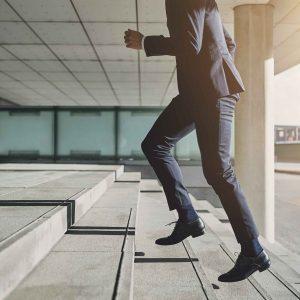Ejecutivo subiendo escaleras corriendo