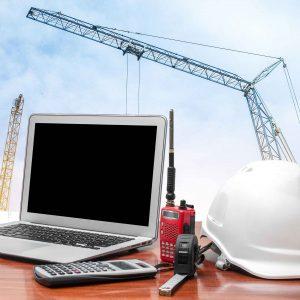 Casco y portátil sobre mesa en frente de obra