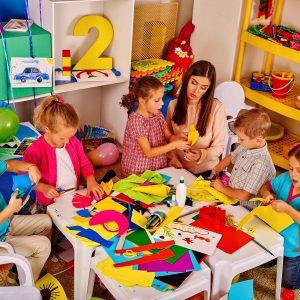 Profesora haciendo manualidades con niños en gardería