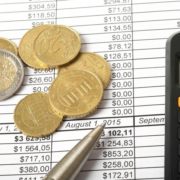 Monedas y calculadora sobre hoja de cálculo