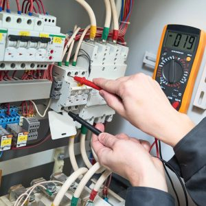 Persona trabajando en cuadro eléctrico