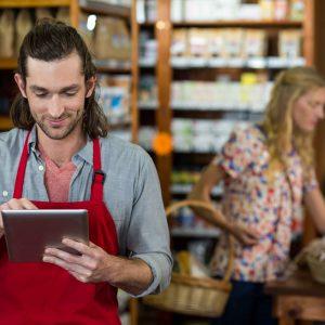 Chico en pequeña tienda con tablet