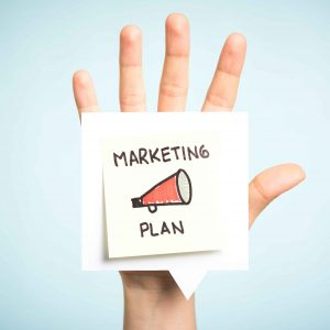 """Post it pegado en una mano con el mensaje """"plan de marketing"""" y un altavoz"""