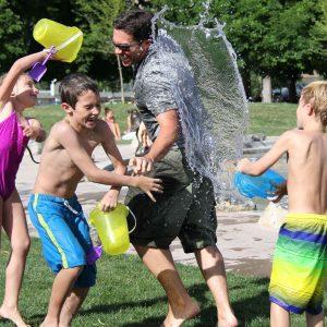 Niños jugando a tirar agua a un monitor