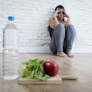 """Chica sentada en el suelo """"huyendo"""" de un plato de comida"""